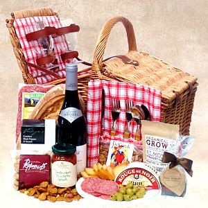 A wicker picnic basket with wine glasses, plates, utensils, cutting board, wine and fine food.