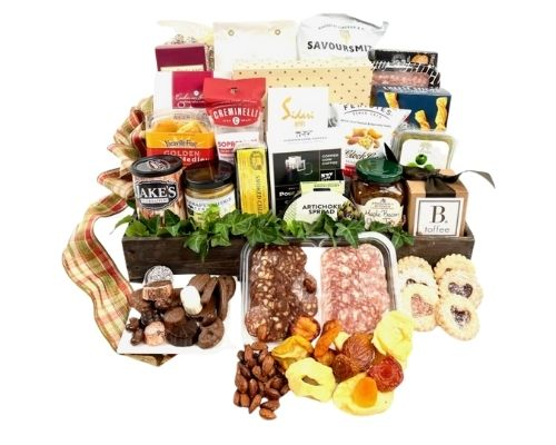 a huge basket with cheeses, crackers, chips, salsa, nuts, chocolate, duck rillettes and much more.