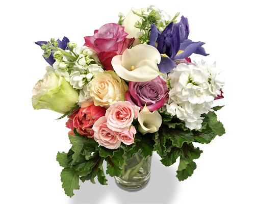 a flower arrangement of ofroses, mini calla lilies, iris and scented gernaium leaves arranged in a glazed pot