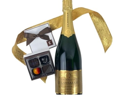 a bottle of J. Lassalle champagne and a box of chocolates wrapped in cellophane with a bow