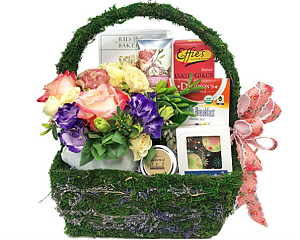 This moss covered gift basket abounds with a floral motif including a fresh flower arrangement and chocolates and other treats