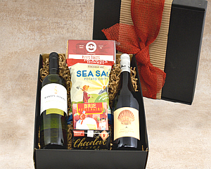 a black gift box with a red bow holds 2 wines, cheese, chocolate, petite toasts and chips