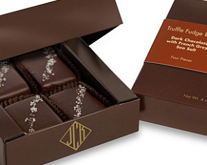 a dark brown box containing 4 pieces of John Kelly fudge truffles with grey sea salt.