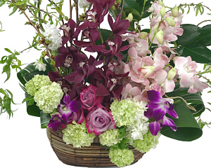 an arrangement of orchids, roses and other flowers in a wicker basket
