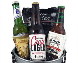 A metal wine bucket with three craft beers and snacks