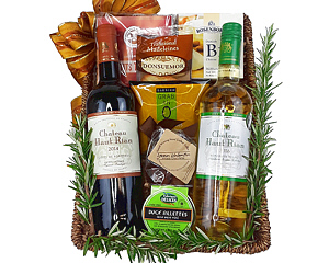 a wine basket with two French wines, cheese, crackers and chocolate