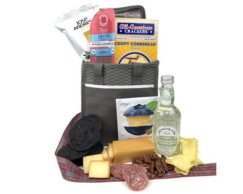 An insulated gray tote with the cheese, salami, Fentiman's Elderflower drink, potato chips and other fun foods.