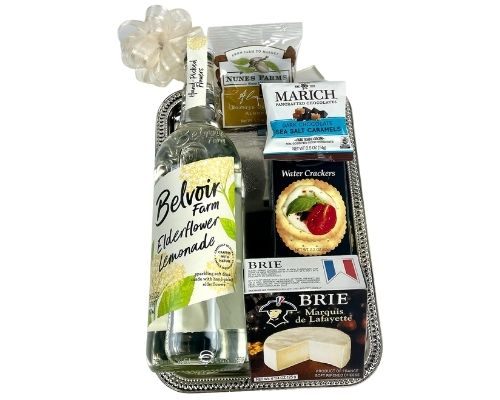 a silver metal serving tray holds a bottle of Elderflower Lemonade with cheese, chocolate, crackers and nuts