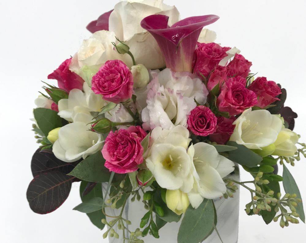 a pink vase full of pink roses with touches of white and lavender flowers