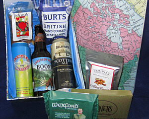 a cardboard box with world map graphic on the lid contains 3 international beers, cheese, crackers and snacks
