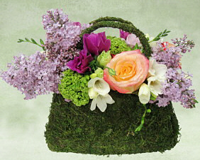 green moss covers a purse shaped container holding an arrangement of roses and seasonal flowers