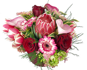 a low vase arrangement of red and pink tulips, roses, gerberas amd a protea
