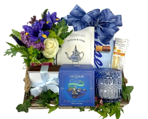 a rectangular wood tray with a tea mug, chocolates, tea biscuits, teas, chocolates, cookies nuts and a vase of flowers