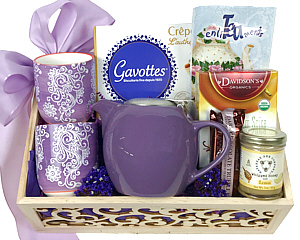 a wood box with an open scroll work front holds a purple teapot, 2 tea mugs, tea, lemon honey, cookies