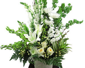 a tall vase with a tall floral arrangement of white and green