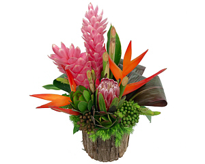 a rustic vase holding a variety of colorful tropical flowers