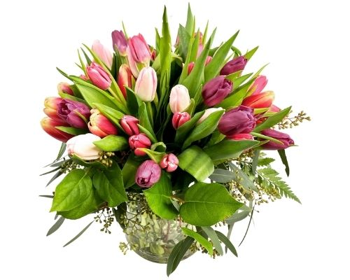 A beautiful arrangement of Tulips and other flowers in a clear glass vase.