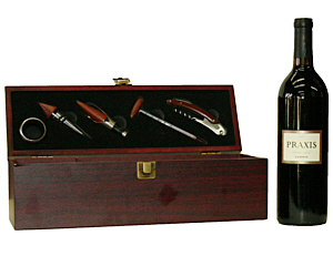 a brown wood wine box shown open, displaying the wine tools which attach to the inside of the lid. A bottle of wine stands next to it.